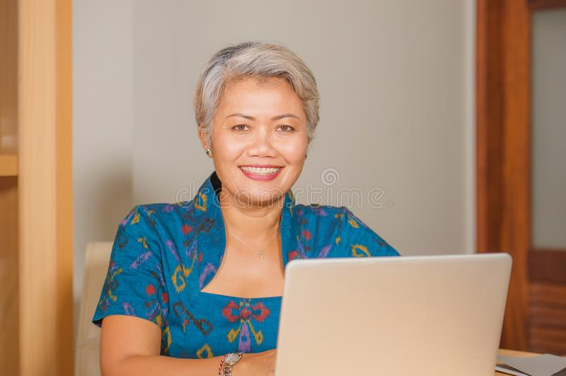 Lifestyle portrait of Happy and attractive elegant middle aged Asian business woman working smiling at office computer desk royalty free stock photography