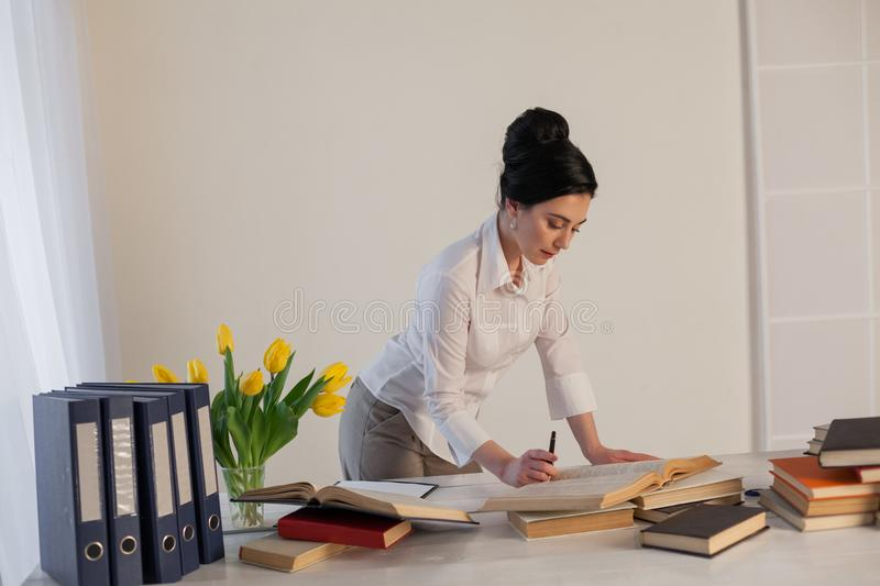 A woman in a business suit reads books in the Office royalty free stock image
