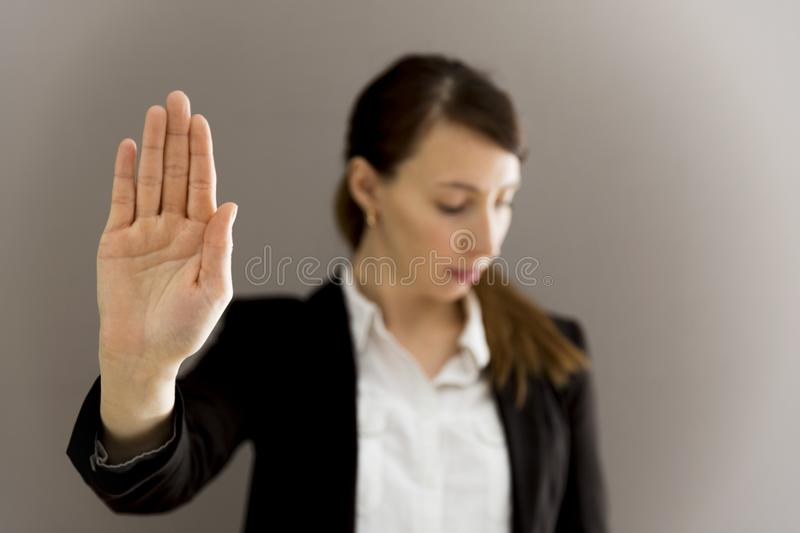 Woman in business suit showing her palm, body language, say NO a. T work, self-awareness stock image