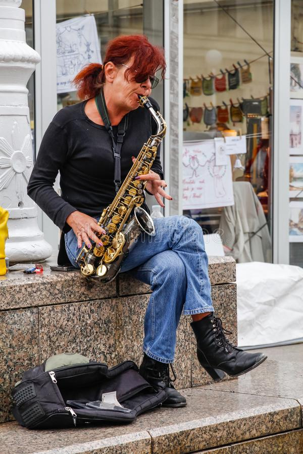 Woman busker playing saxophone on a street in Zagreb stock images