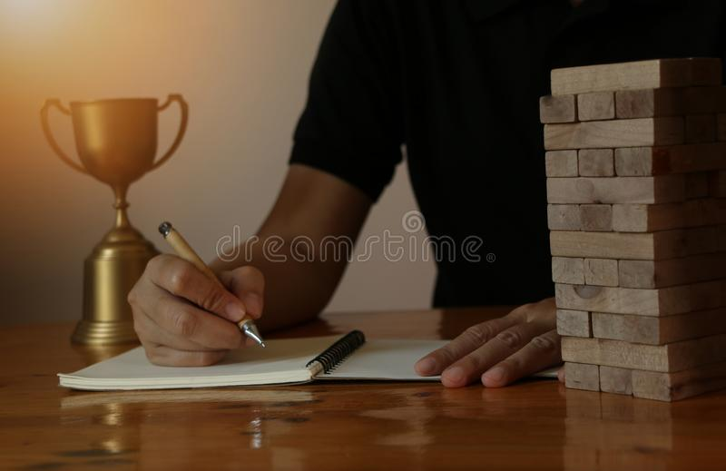 Woman bussiness hand writeing on note book with block wooden game on wooden table royalty free stock photography