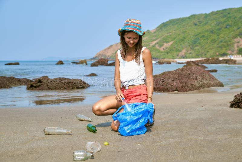 Woman busy collecting rubbish, holds garbage bag stock image