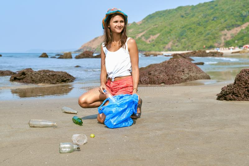 Woman busy collecting rubbish, holds garbage bag royalty free stock image