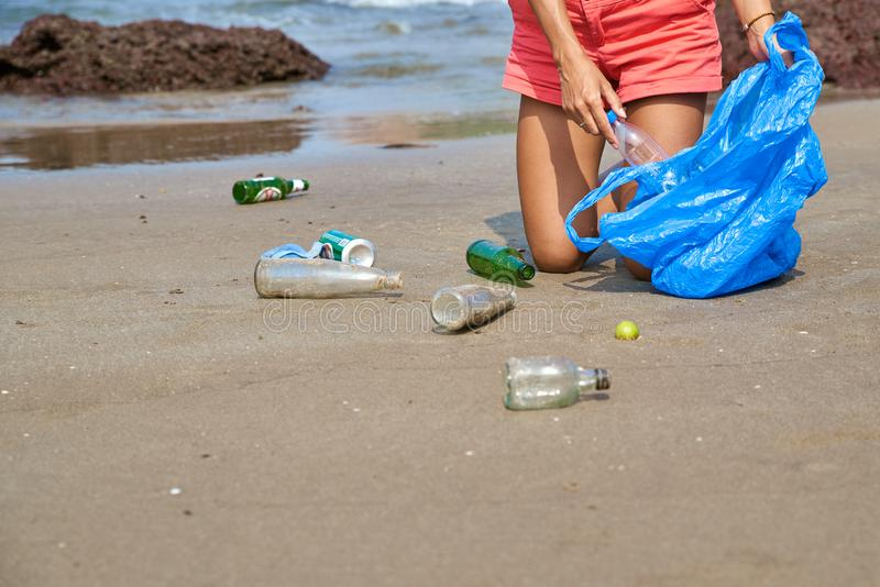Woman busy collecting rubbish, holds garbage bag. Care about nature. Young woman tourist volunteer busy collecting rubbish, picks up plastic bottles, protects royalty free stock images