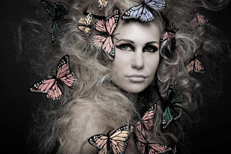 Woman with butterfly in big curly hair on black. stock photos