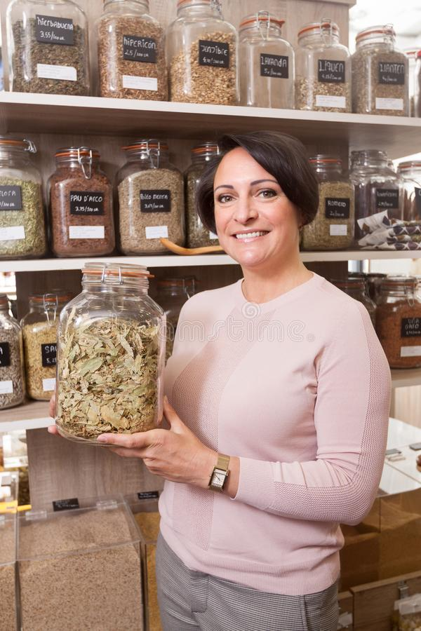 Woman buyer selects herbs in store of ecological products. Ordinary woman buyer selects herbs in store of ecological products stock photography