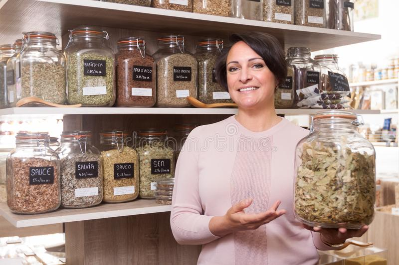 Woman buyer selects herbs in store of ecological products. Ordinary woman buyer selects herbs in store of ecological products stock photo