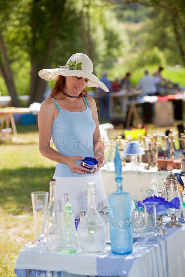 Woman buying antique collectibles, Provence, France. Attractive young woman in a summer sunhat buying antique collectibles at an outdoor stall at an open-air stock photos