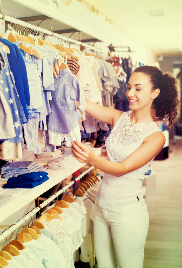 Woman buying baby clothes. Smiling woman buying baby clothes in blue color in apparel shop royalty free stock image