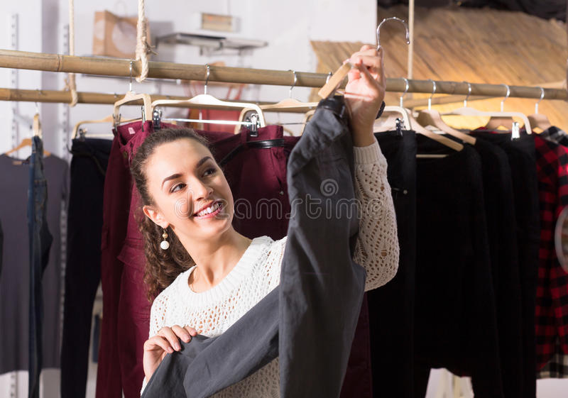 Woman buying breeches at the store. Smiling brunette girl selecting new breeches at the store royalty free stock photos