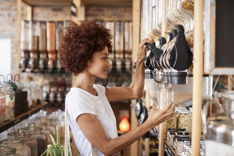 Woman Buying Cereals And Grains In Sustainable Plastic Free Grocery Store royalty free stock photos