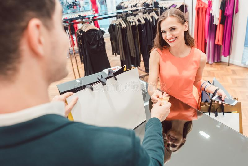 Woman buying fashion dresses she shopped in store. Talking to sales clerk royalty free stock photos