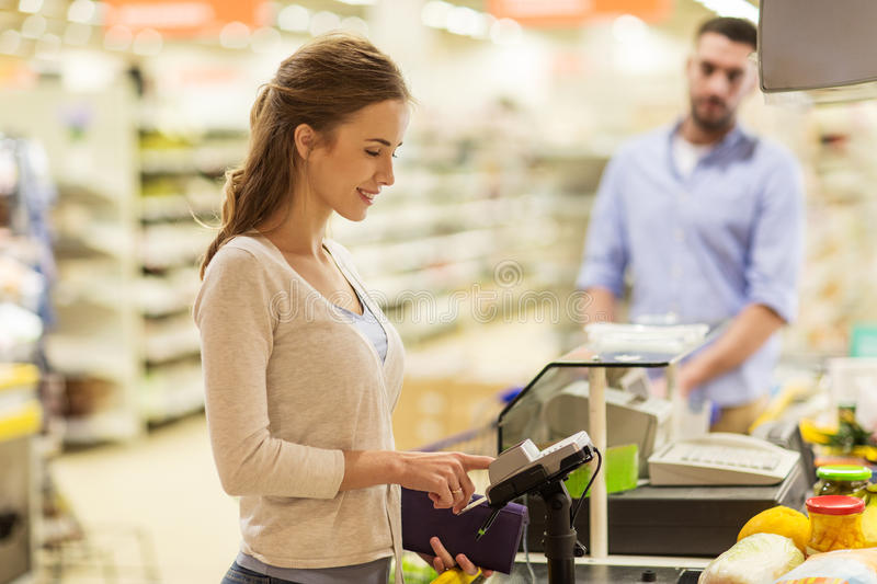 Woman buying food at grocery store cash register. Shopping, sale, consumerism, cashless payments and people concept - happy women buying food at grocery store or royalty free stock images
