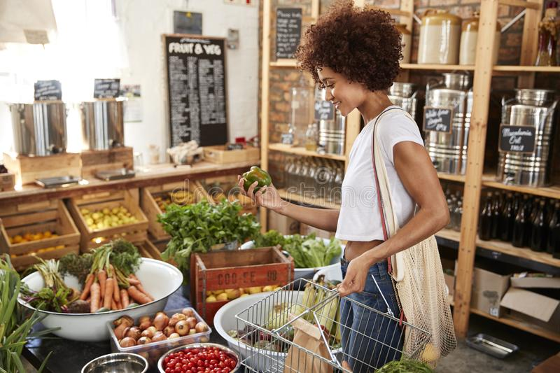 Woman Buying Fresh Fruit And Vegetables In Sustainable Plastic Free Grocery Store stock images