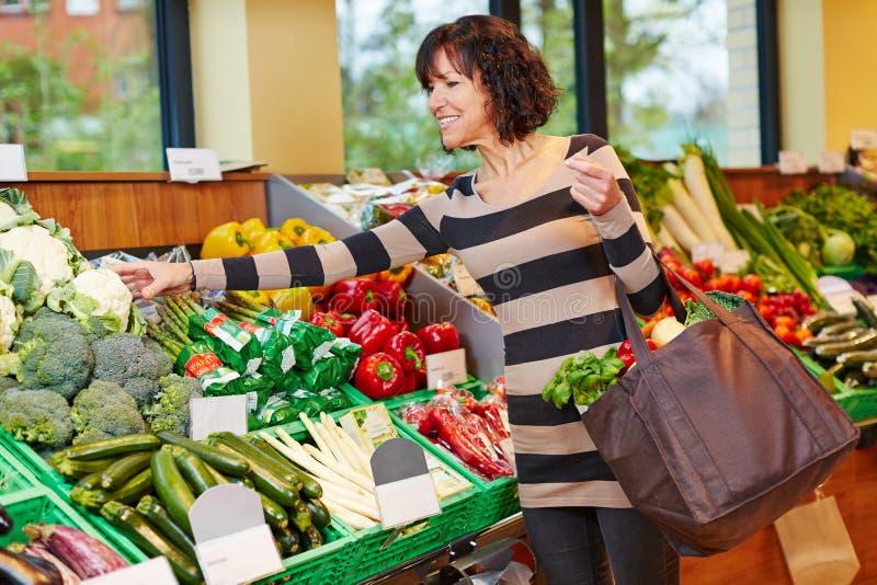 Woman buying fresh vegetables stock photos