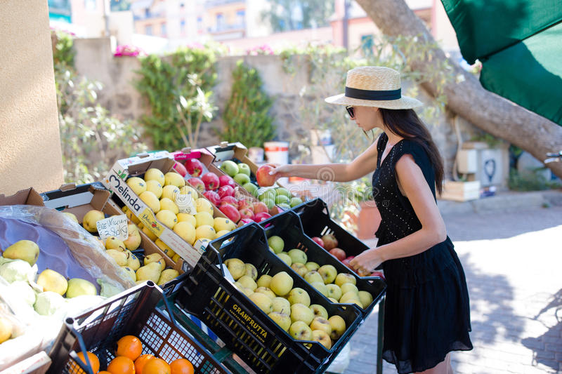 Woman buying fruits and vegetables at farmers outdoor market. Portrait of young woman shopping for healthy lifestyle. Woman buying fruits and vegetables at royalty free stock images