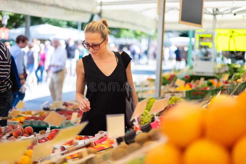 Woman buying fruits and vegetables at local food market. Market stall with variety of organic vegetable stock images
