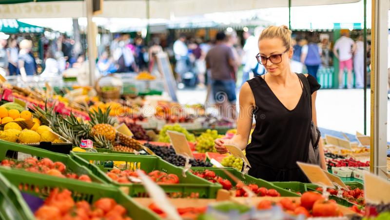Woman buying fruits and vegetables at local food market. Market stall with variety of organic vegetable stock image