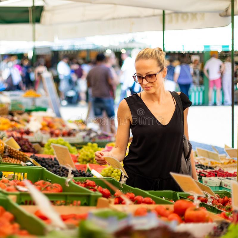 Woman buying fruits and vegetables at local food market. Market stall with variety of organic vegetable stock photos