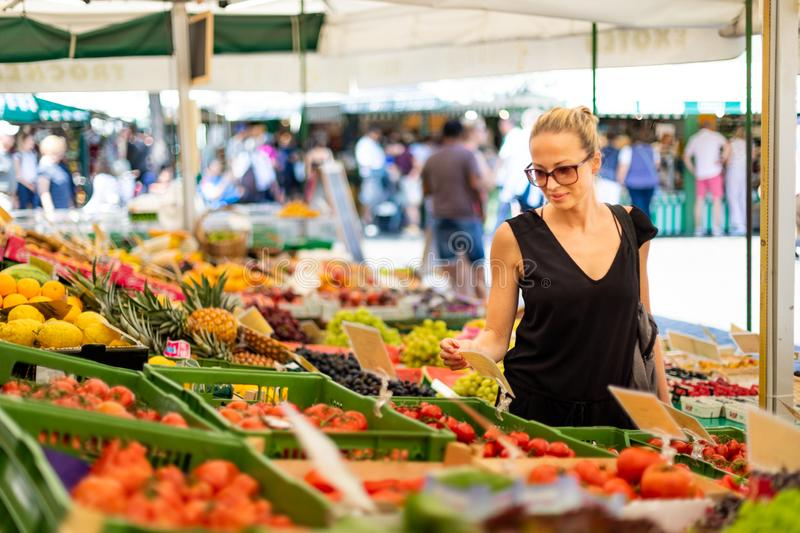 Woman buying fruits and vegetables at local food market. Market stall with variety of organic vegetable royalty free stock photography