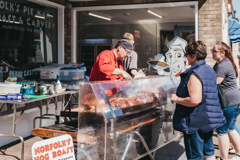 Woman buying hog roast from a street food market stall in Sheringham, Norfolk, UK stock photography