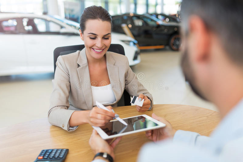 Woman buying a new car. Car dealer with a female buyer stock image