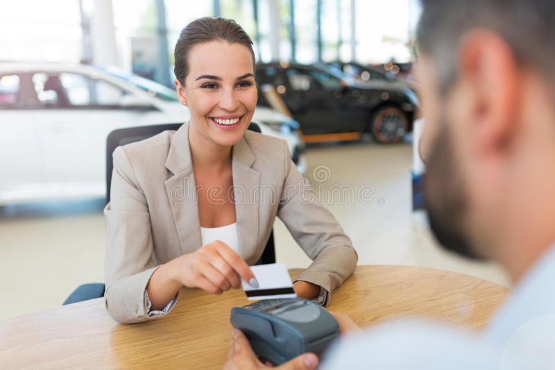 Woman buying a new car. Car dealer with a female buyer royalty free stock photo