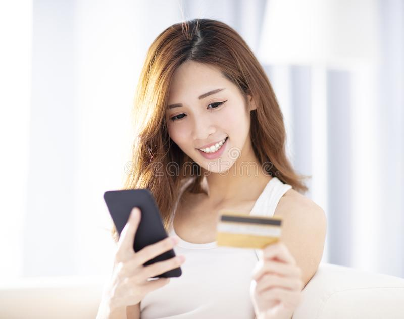 Woman buying online with  credit card and smart phone royalty free stock photography