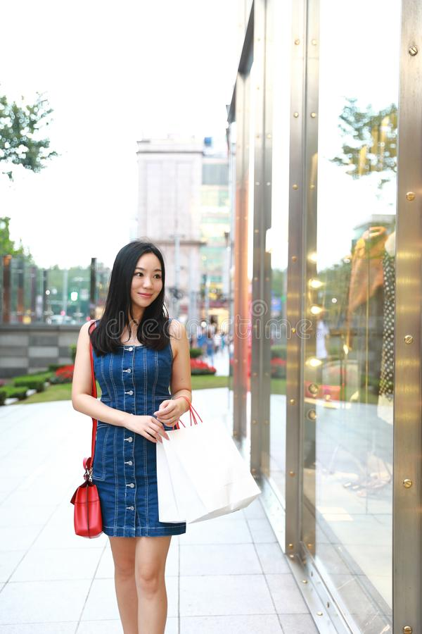 Happy Asia Chinese Eastern oriental young trendy woman girl shopping in mall with bags look at shopping window on street city stock image