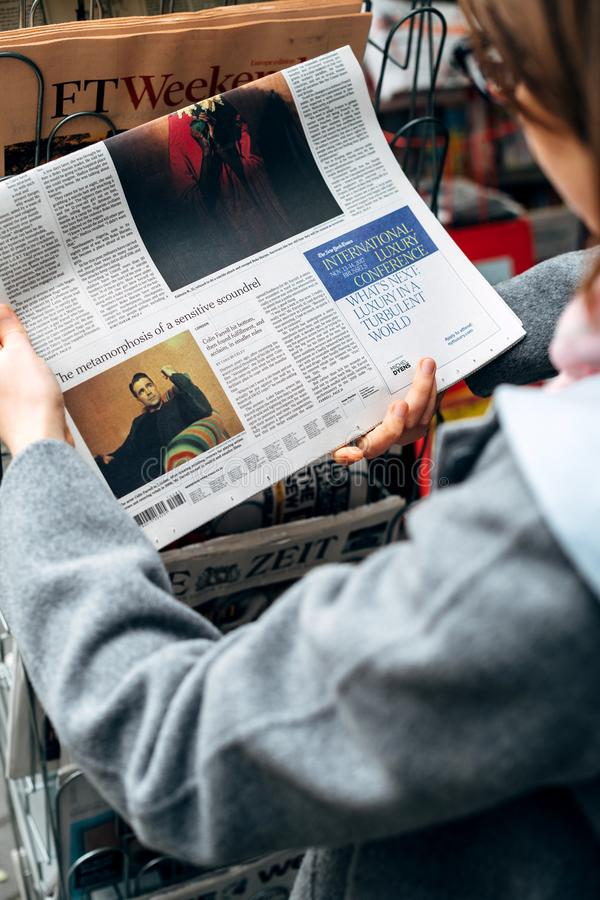 Woman buying reading The New York Times about Collin Farrell royalty free stock image