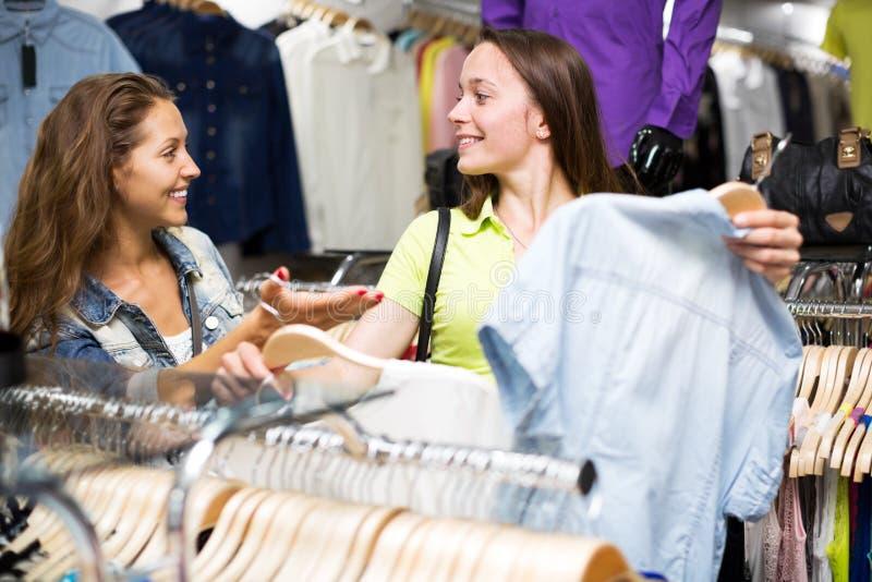 Woman buying shirt. Happy women buying shirt in shopping center for her husband stock photo