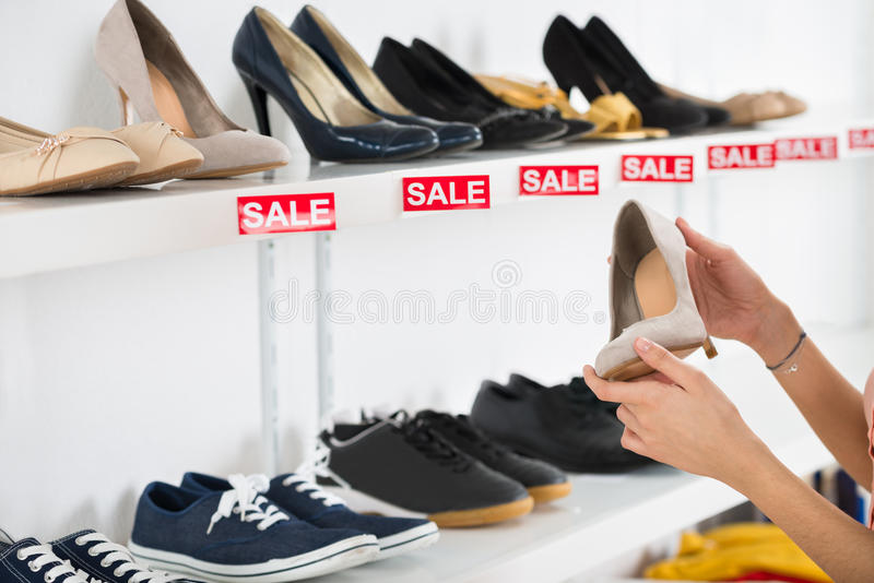 Woman Buying Shoe In Retail Store stock photos