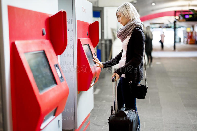 Woman Buying Train Ticket Using Vending Machine At Station. Side view of young woman with luggage buying train ticket using vending machine at station stock photos