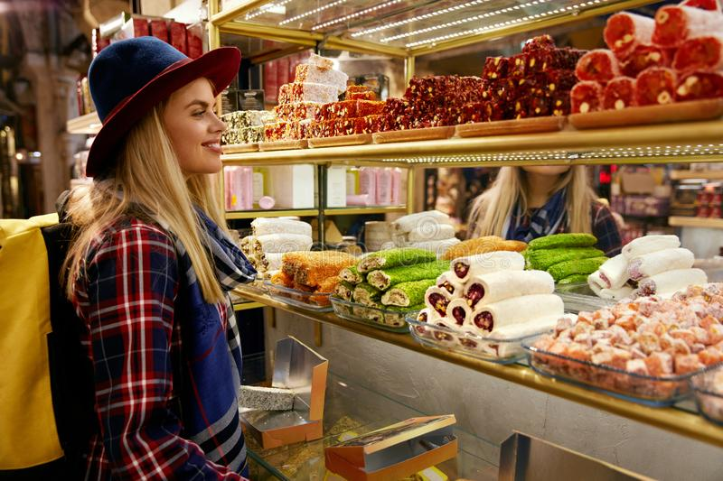 Woman Buying Turkish Sweets At Eastern Food Market. Girl Near Showcase With Desserts. High Resolution royalty free stock photography
