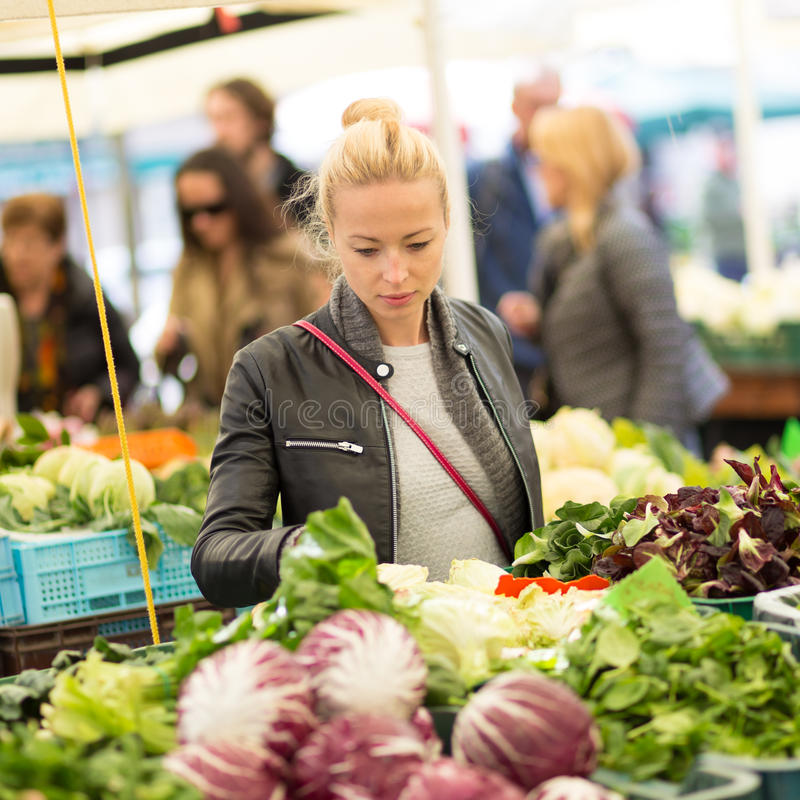 Woman buying vegetable at local food market. stock image