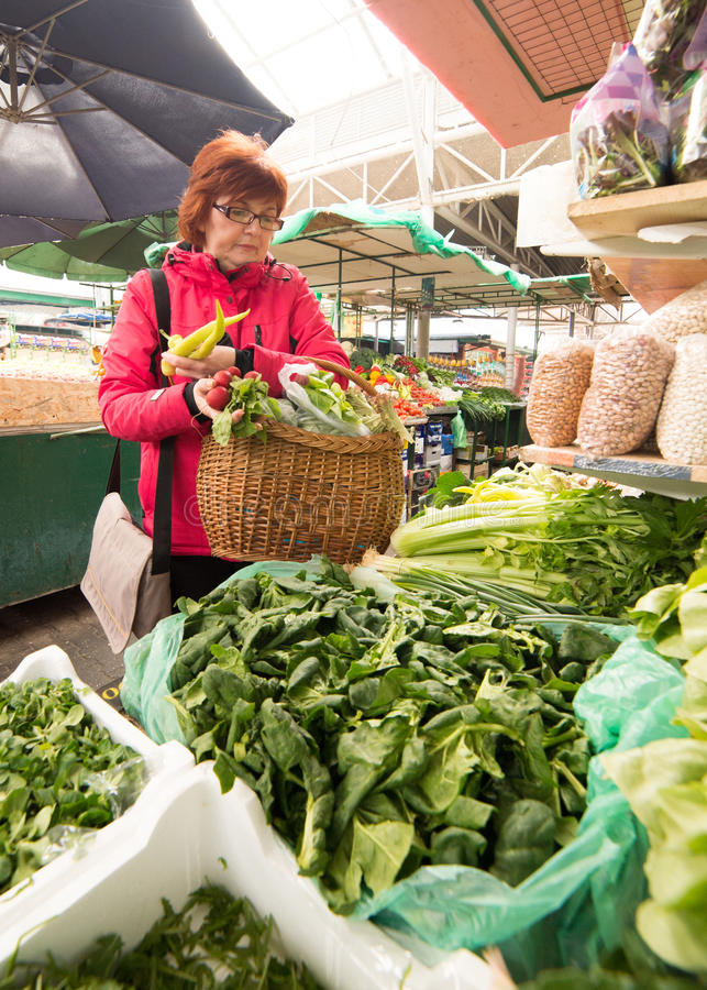 Woman buying vegetables at market place royalty free stock image