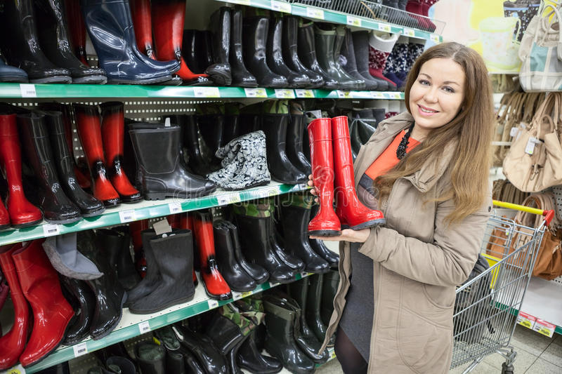 Woman buying waterproof shoes in shopping center royalty free stock photos
