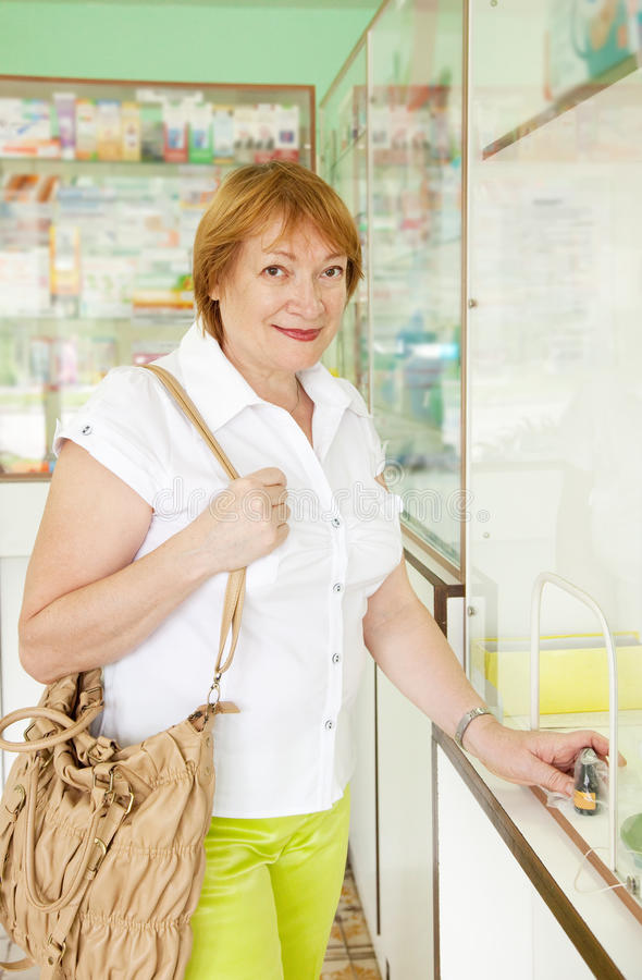 Woman buys drugs at pharmacy. Mature woman buys drugs at the pharmacy stock images