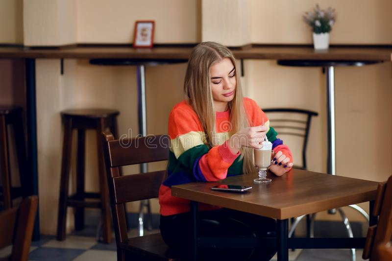 A woman in a cafe is drinking coffee, a beautiful sweater is on the girl, a beautiful young girl is waiting for her man royalty free stock photography