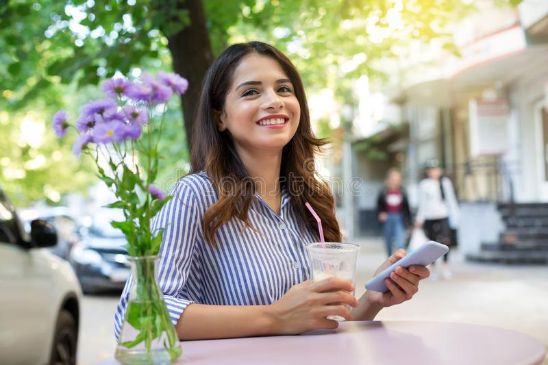 Woman in a cafe drinking coffee, holding a phone and looking at the camera. Copy space stock photography