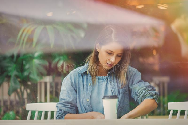 Woman in a cafe and drinking coffee while sitting by the window stock photography