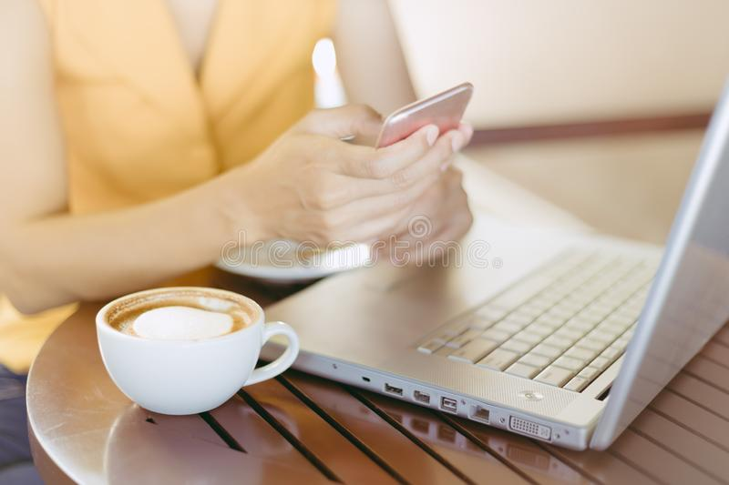 Woman at cafe drinking coffee and use mobile phone at use network for business. stock image