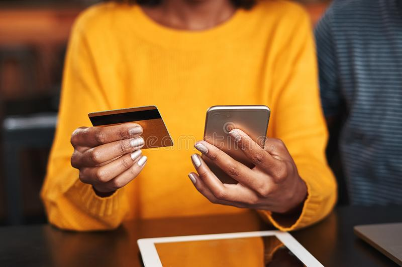 Woman in a cafe shopping online with credit card. Close-up of a young woman in cafeteria using mobile phone and credit card for shopping online royalty free stock photos