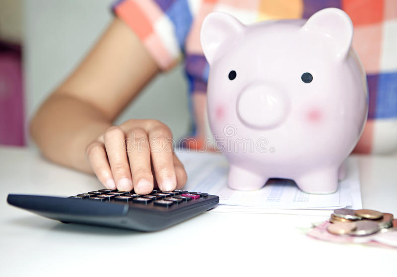 Woman calculate expenses. Women calculate expenses with calculator and piggy-bank royalty free stock image