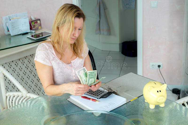 Woman calculate housekeeping allowance. Blond woman calculate housekeeping allowance in living room royalty free stock image