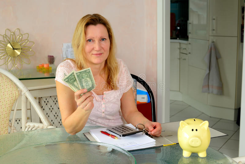 Woman calculate housekeeping allowance. Blond woman calculate housekeeping allowance in living room royalty free stock photos