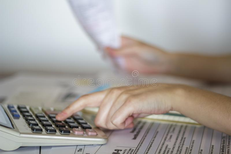 Woman calculates value of receipts for taxation purposes.  stock images