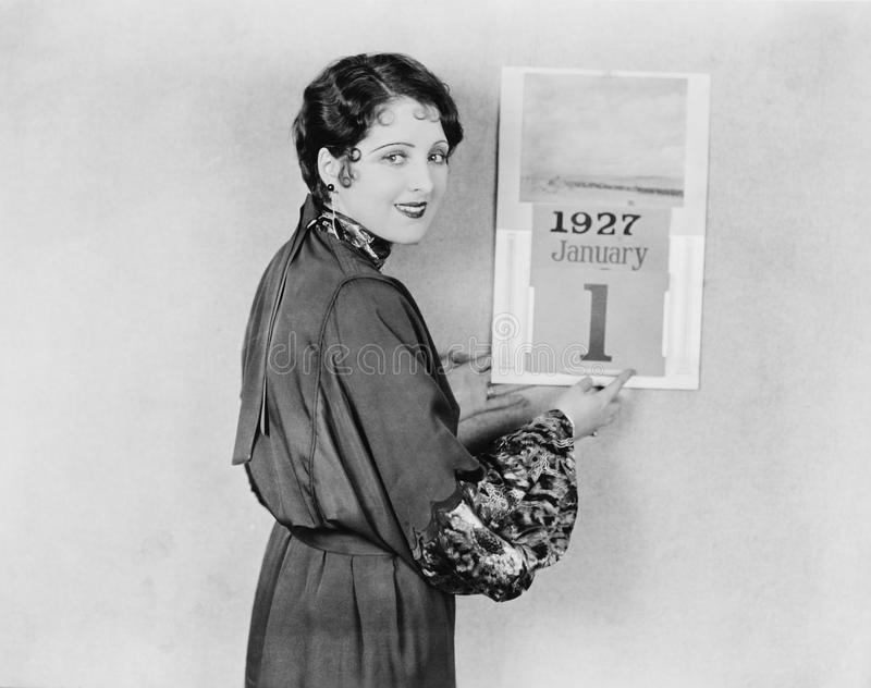 Woman with calendar on New Years Day. (All persons depicted are no longer living and no estate exists. Supplier grants that there will be no model release royalty free stock image