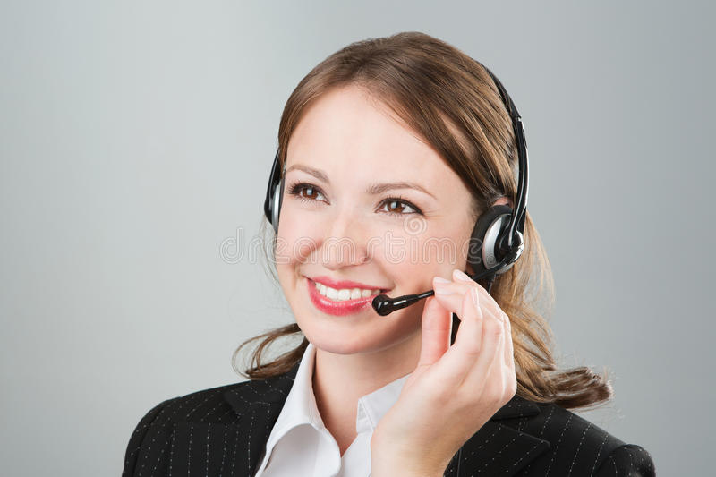 Woman call center employee. Speaking over the headset. Beautiful young call center worker wearing a headset. Call center operator against grey background. Studio stock photos