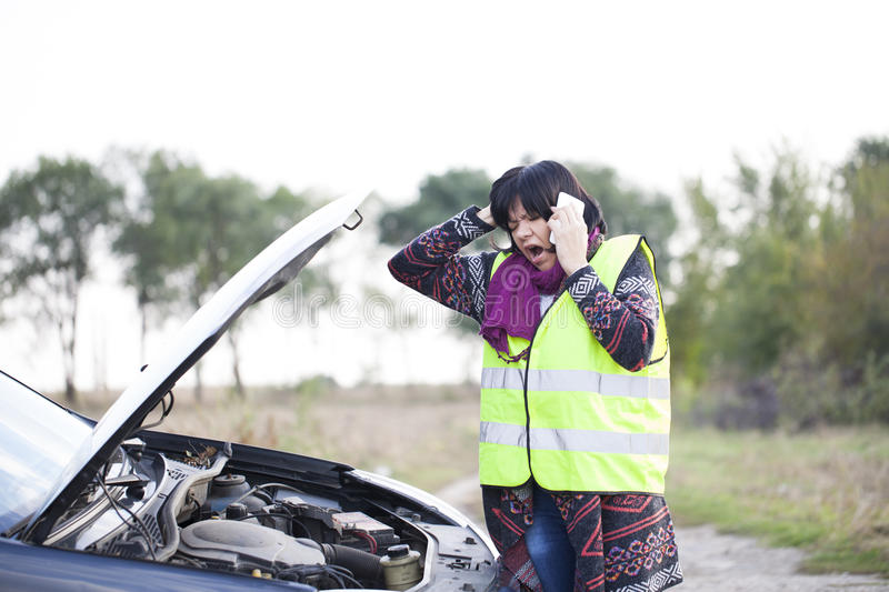 Woman call for help because of a malfunction the car on the road royalty free stock photo